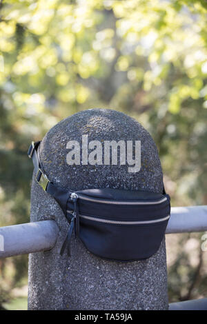 A traveler left their waist bag on the railing protrusion. Mid shot - Stock Image