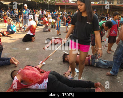 Navotas City, Philippines. 4th Jan, 2012. A young lady seen serving as an executioner to a flagellate crawling on the pavement during Good Friday. Credit: Josefiel Rivera/SOPA Images/ZUMA Wire/Alamy Live News - Stock Image