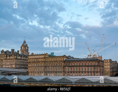 Cityscape  of Edinburgh grand buildings in Winter dawn. Rocco Forte Balmoral Hotel with clock tower and Waverley station glass roof. - Stock Image