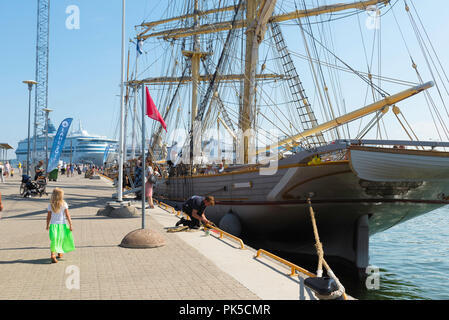 Child harbor ship, rear view of a small child in a green skirt walking beside a 19th Century sailing ship in Tallinn harbor on a summer day, Estonia. - Stock Image