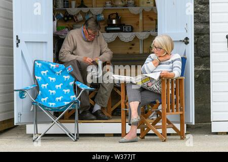 Lyme Regis, Dorset, UK.  13th July 2019. UK Weather.  A couple reading newspapers at a seafront beach hut at the seaside resort of Lyme Regis in Dorset on a warm cloudy day.  Picture Credit: Graham Hunt/Alamy Live News - Stock Image