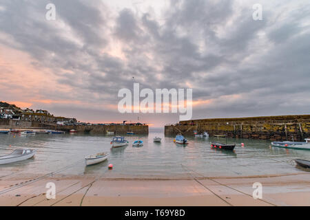 Mousehole, Cornwall, UK. 30th April 2019. UK Weather. The sun briefly showed itself on the horizon, on the Cornish coastline at Mousehole this morning,  then dissapeared behind thick clouds. Credit Simon Maycock / Alamy Live News. - Stock Image