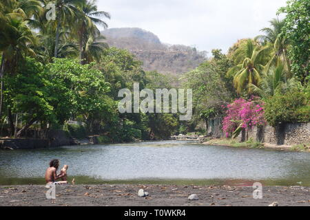 Man bathing child in river with tropical scenery in Central America - Stock Image
