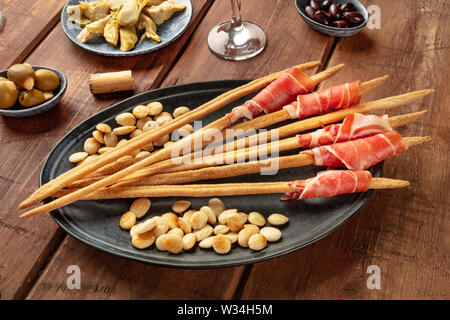 Italian antipasti. Grissini with parma ham and roasted almonds, with olives and artichokes, on a dark rustic wooden background - Stock Image