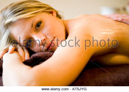 Pretty young woman receiving relaxing massage in lifestyle surroundings - Stock Image