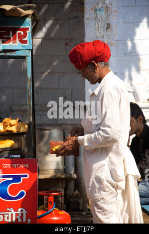 Rajasthani man in distinctive white dress and red tuban buying from a street stall. Pushkar, Rajasthan, India - Stock Image