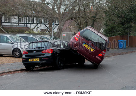 Fleet, Hampshire, UK. 23rd November 2018. A Mercedes A150 turning right onto Kent Road, Fleet managed to drive over a BMW 118D parked opposite. Police at the scene confirmed that, although shaken, the occupants of both vehicles were not seriously injured. Credit: Images by Russell/Alamy Live News - Stock Image