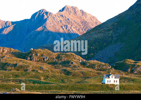 A white house is dwarfed by craggy mountains in the village Hovden on Vesterålen in northern Norway. - Stock Image