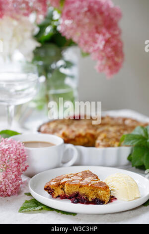 Blackcurrant and almond cake with vanilla ice cream - Stock Image