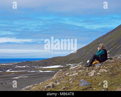 Bird watching at Isbjornhamna, below the bird cliffs of Spitsbergen, Svalbard, Norway. - Stock Image