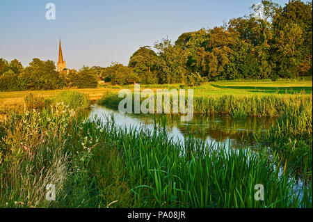 The River Windrush winding through water meadows towards the Cotswold town of Burford, with the church spire of St John the Baptist in the distance. - Stock Image