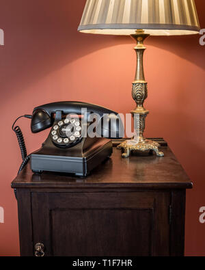 'Old telephone and lamp on bedside table in The Zetter Townhouse in London, England' - Stock Image