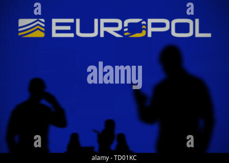 The Europol logo is seen on an LED screen in the background while a silhouetted person uses a smartphone in the foreground (Editorial use only) - Stock Image