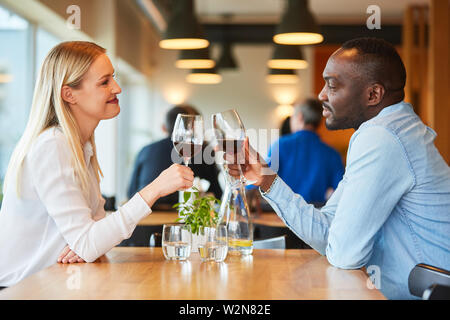 Multicultural young couple having a drink while having a rendezvous in the restaurant - Stock Image