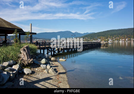 Pier at Rocky Point Park in Port Moody, BC, Canada on a sunny Autumn day.  Burrard Inlet and mountains, Metro Vancouver urban park. - Stock Image