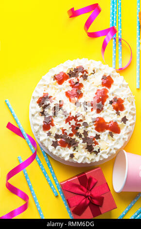 Sponge layer birthday cake with whipped cream frosting milk chocolate star sprinkles strawberry jam. Pink paper drinking cups blue straws gift box on  - Stock Image