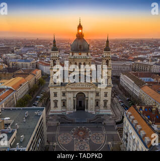 Budapest, Hungary - Aerial view of famous St. Stephen's Basilica in the morning with golden amd blue sky and rising sun at right behind the building - Stock Image