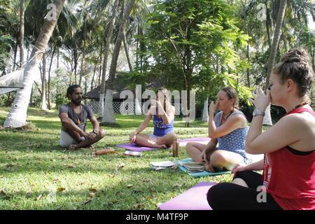 Indian Yoga trainer teaching pranayama in Kerala, India - Stock Image