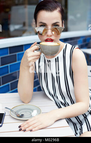 Woman in striped minidress drinking outside cafe, close up - Stock Image