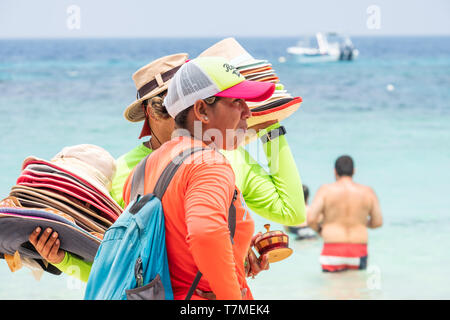 Local beach vendors selling their wares to tourists in West Bay Roatan Honduras. - Stock Image