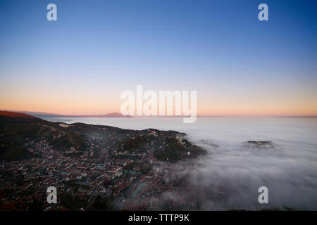 Scenic view of cloudscape over city against blue sky - Stock Image