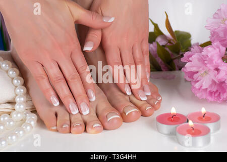 Girl feet and hands with french nail polish in spa salon with decorative pink flower, candles, pearls and towel. Girl pedicure and manicure concept - Stock Image