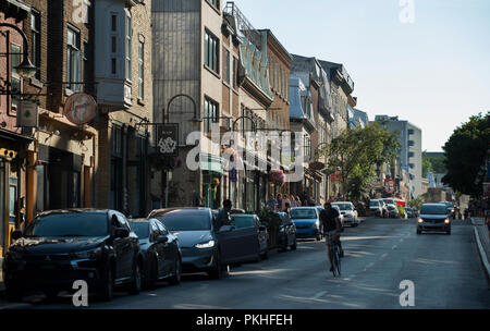 Bicyclist and tourists on Rue Saint-Jean on a summer evening in old Québec City in the Saint-Jean-Baptiste area of old Québec City, Canada. - Stock Image
