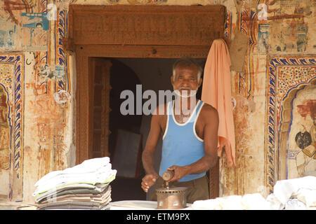Indian man ironing shirts. Mandawa, Shekawati region, Rajasthan India - Stock Image