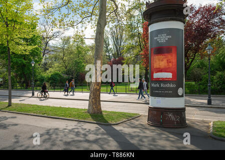Vienna city centre, summer view of Viennese people walking along the Ringstrasse with a typical advertising pillar sited on the right, Wien, Austria - Stock Image