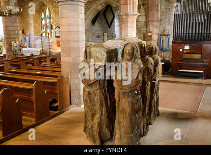 Wood sculpture of monks carrying dead monk in coffin in the nave of The Parish Church of Saint Mary the Virgin on Holy Island of Lindisfarne England - Stock Image
