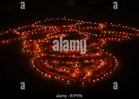 Traditional earthen lamps beautifully setup in a design on a lawn at night, during Diwali festival in India. - Stock Image