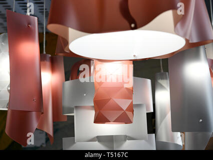 Modern plastic chandeliers of red and silver colors with geometrical shape design and glowing lamps, hanging on white wires. Viewed in close-up from l - Stock Image
