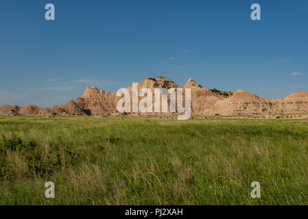 Wide View of Badlands Formation with Grassy Field - Stock Image