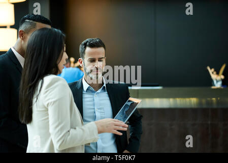 Business people discussing on laptop in hotel lobby - Stock Image