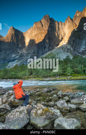 Outdoor photographer taking pictures of the beautiful scenery in Romsdalen valley, Møre og Romsdal, Norway. - Stock Image