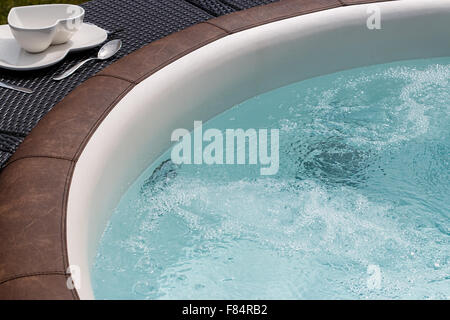 Luxurious standalone hot tub or jacuzzi with hot bubbling water - Stock Image