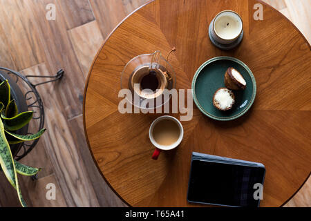 A top down shot of modern living room coffee table with a coffee cup, book, tablet, and a muffin on it. - Stock Image