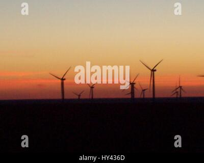 Silhouette Windmills On Landscape Against Sky During Sunset - Stock Image