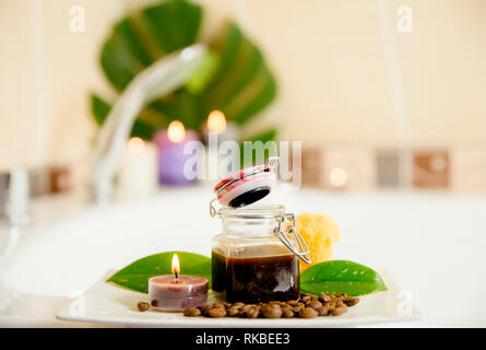 Coffee scrub mixture in glass jar for using many purposes: face, hair, body mask and scrub concept, indoors in home bathroom, candles lit flames on th - Stock Image