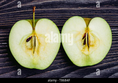 Ripe apple on a wooden table cut in half - Stock Image