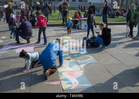 Children draw on the pavement with coloured chalks on Parliament Square, Westminster for the Extinction Rebellion demonstration - Stock Image