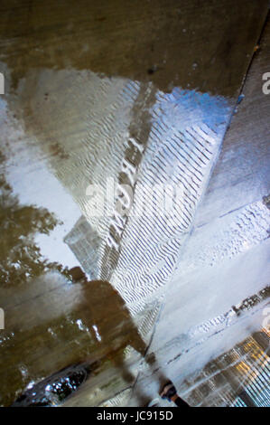 Chicago, United States. 14th Jun,  2017. A wet man and Trump tower are reflected in a rain puddle as the thunder - Stock Image
