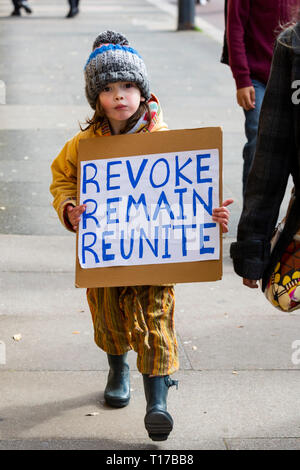London, UK. 23 March 2019. A young child carries a placard with the words: revoke, remain, reunite. Remain supporters and protesters take part in a march to stop Brexit in Central London calling for a People's Vote. - Stock Image