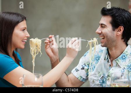 Couple feeding each other spaghetti - Stock Image