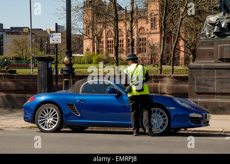 A parking attendant issuing a parking ticket on Kelvin Way, Glasgow, Scotland, UK - Stock Image