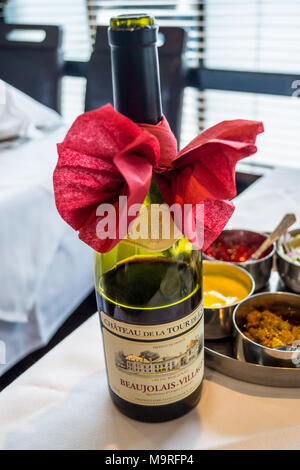 A bottle of Beaujolais-Villages red wine with decorative bow, Spice Masala indian restaurant, formerly Kismet Tandoori, Chipping Ongar, Essex, England - Stock Image