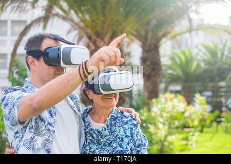 Adult couple mixed generations diversity have fun together in outdoor using goggles headset for virtual reality - people and technoogy concept - Stock Image