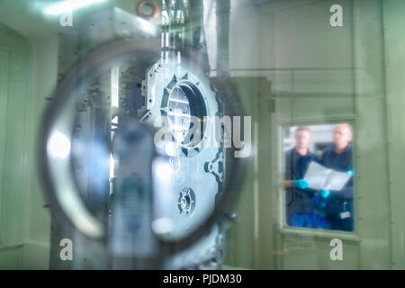 Engineers viewing part inside CNC machine in gearbox factory - Stock Image