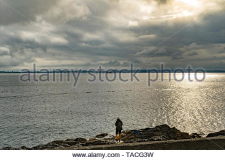 Newlyn, Cornwall , UK. 24th May 2019. UK Weather.  The sun just breaking through thick clouds this morning, as a fisherman stands on the rocks at Newlyn. Credit Simon Maycock / Alamy Live News. - Stock Image