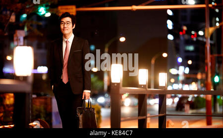 Smiling businessman standing against night view of city - Stock Image